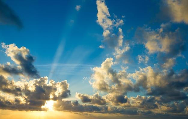 Zonsondergang met zonnestralen, lucht met wolken en zon