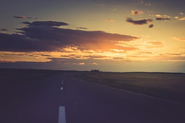 Zonsondergang of een zonsopgang over de weg die in de verte gaat.