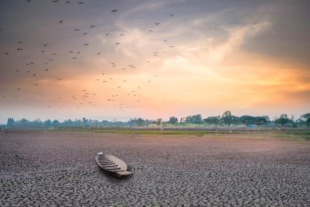 Zonsondergang of zonsopgang met dor land en vissersboot