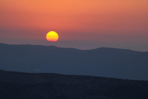 Zonsondergang op de berg, ondergaande zon achter de berg.