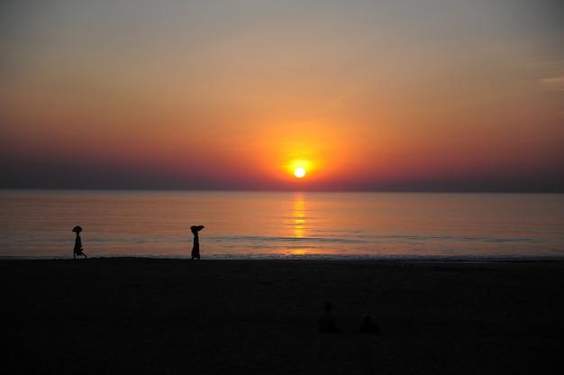 Zonsondergang op de indische oceaan, avondhemel in rode en oranje kleuren. silhouetten van mensen tegen de zee en de ondergaande zon. twilight op de kust in de tropen