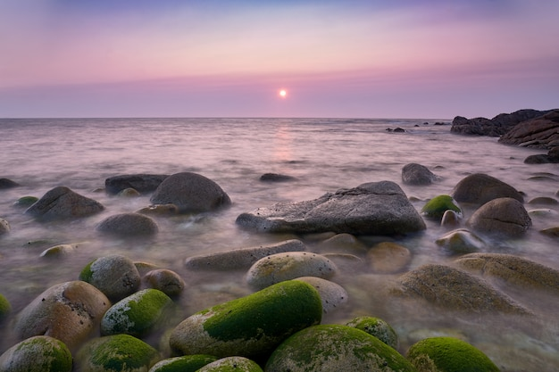 Zonsondergang op de kust van galicië met ronde groene rotsen