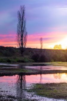 Zonsondergang op de rivieroever, warme kleuren met reflectie