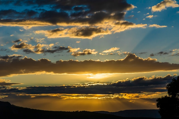 Zonsondergang op een dag met wolken en zonnestralen die eruit komen in de berg.