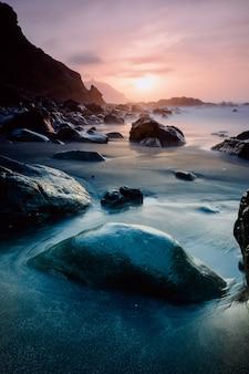 Zonsondergang op een rotsachtig strand