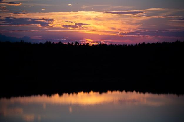 Zonsondergang op het meer in pastelkleuren. het bos wordt weerspiegeld in het water. er is kopieerruimte.