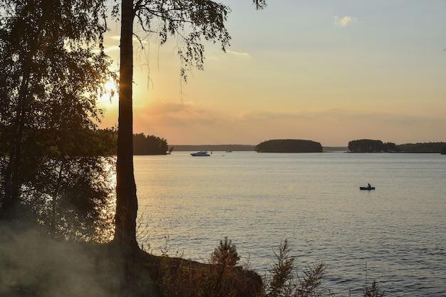 Zonsondergang op het pestovo-reservoir, zonsondergang op het meer, silhouet van berk