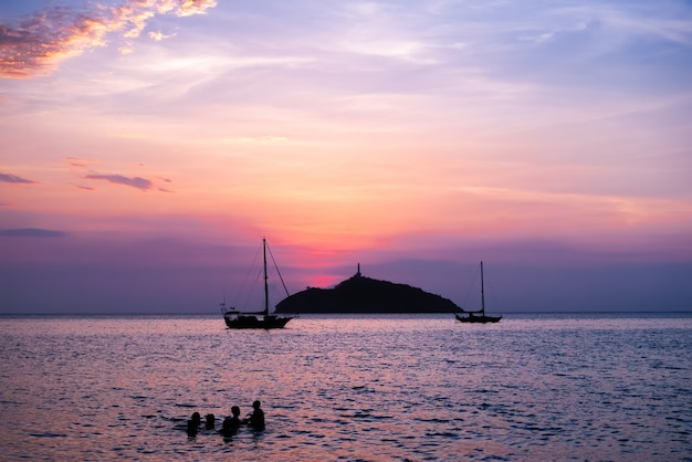 Zonsondergang op het strand met een eilandje in de zee en mensen die zwemmen