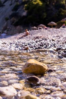 Zonsondergang op het strand. water dat de rotsen aan de kust bedekt.