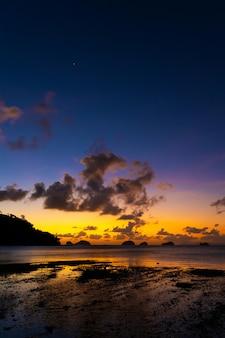 Zonsondergang op het tropische strand. oranje zonsondergang op de oceaan. kleurrijke zonsondergang in de tropen