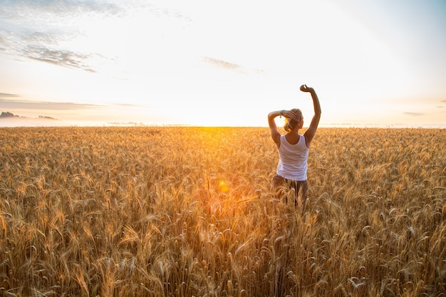 Zonsondergang op het veld met jonge rogge of tarwe in de zomer