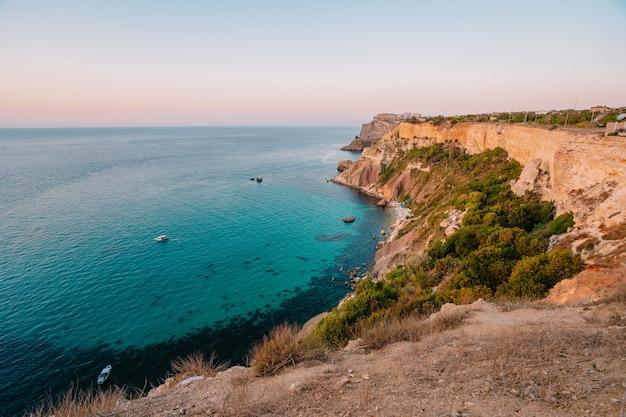 Zonsondergang op kaap fiolent, panorama van de zwarte zee met azuurblauw water, de krim