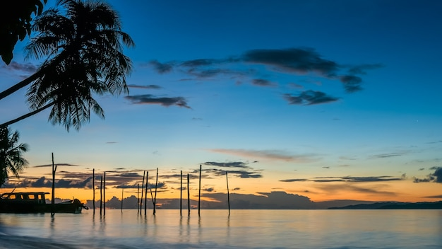 Zonsondergang op kri island. boten onder palmbomen. raja ampat, indonesië, west-papoea