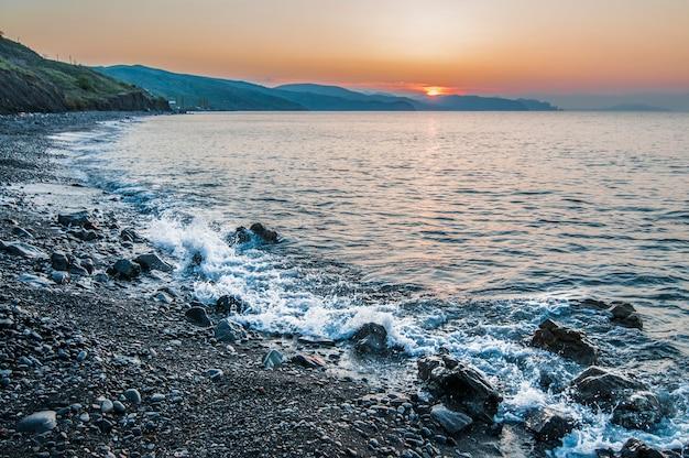 Zonsondergang op kust, rotsachtig strand en blauwe hemel.