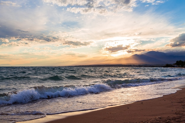 Zonsondergang op zee, prachtige bergen en wolken