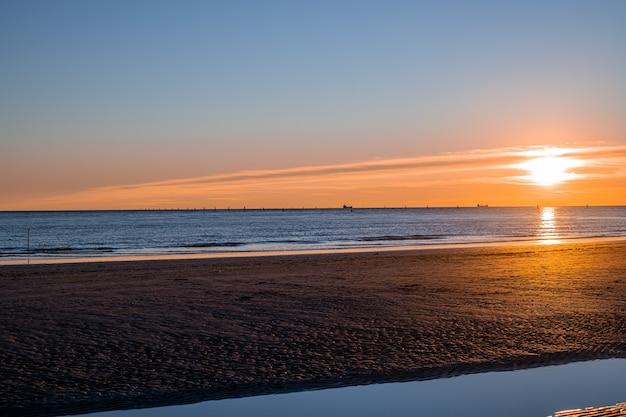 Zonsondergang op zee, zon op hetzelfde niveau als de zee en toevallige passanten