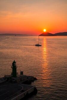 Zonsondergang over de adriatische zee en zijn boten spelen in de reflecties bij de ingang van de haven van split in kroatië.