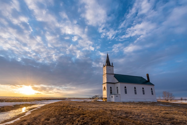 Zonsondergang over de historische zion lutheran church of the flowing well in saskatchewan, canada