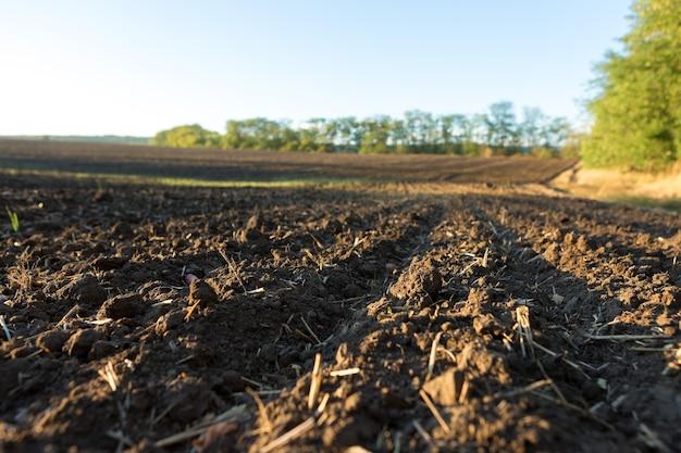 Zonsondergang over een geploegd veld met bruine grond. prachtig herfstlandschap.