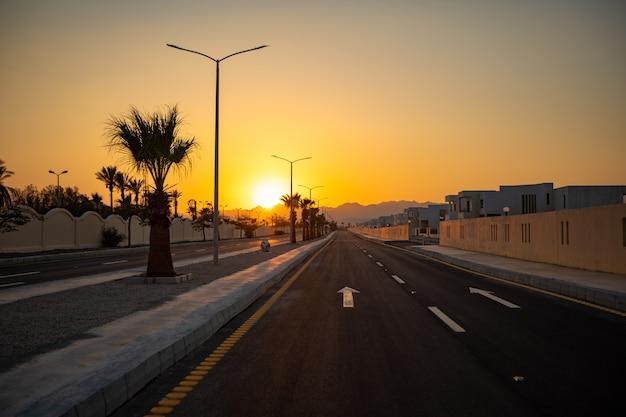 Zonsondergang over een verlaten snelweg met witte wegmarkeringen.