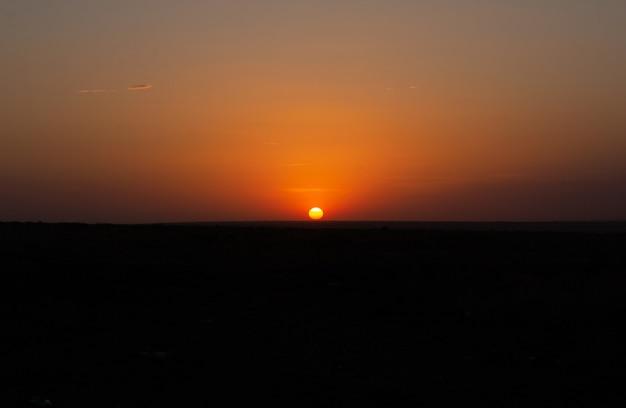 Zonsondergang over een weide, wilde steppe, in het zomerseizoen. landschap
