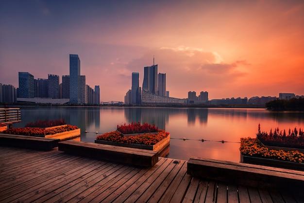 Zonsondergang over het financiële bedrijfsdistrict van het zwaanmeer, hefei-stad, anhui-provincie, china