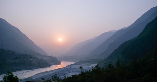Zonsondergang over indus-rivier en lagen van karakoram-bergketen, pakistan.