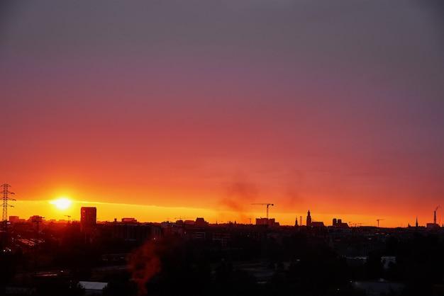 Zonsondergang over stad met gebouwensilhouet