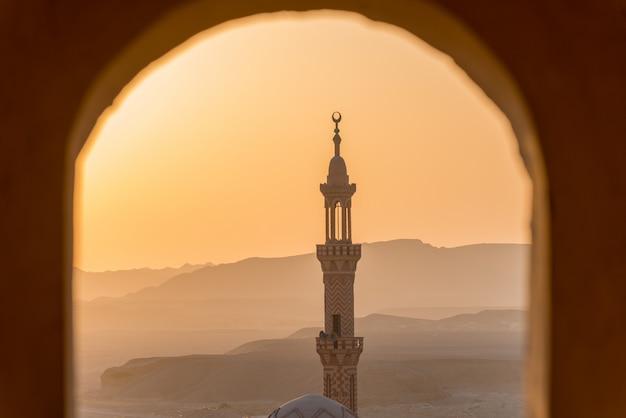 Zonsondergang over woestijn met moslimmoskee op de voorgrond