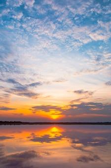 Zonsondergang reflectie lagune. prachtige zonsondergang achter de wolken en de blauwe hemel boven het landschap van de lagune. dramatische hemel met wolk bij zonsondergang