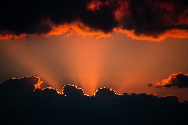 Zonsondergang van onderaf komen lichtstralen uit de wolken en wolken hangen van boven kopieer de ruimte