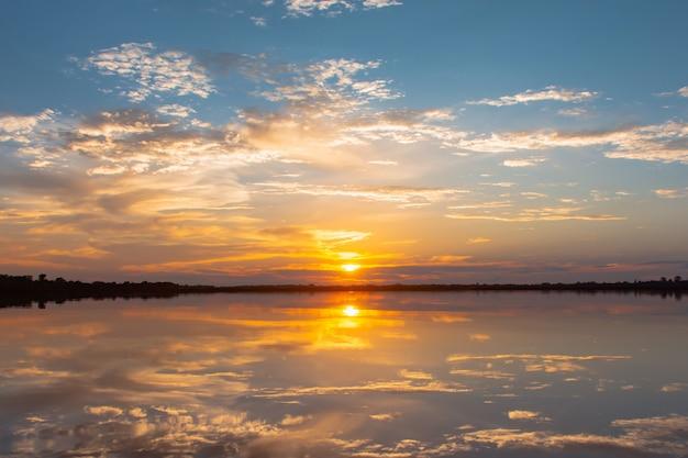 Zonsondergang weerspiegeling lagune. prachtige zonsondergang achter de wolken en de blauwe lucht boven het landschap van de lagune. dramatische hemel met wolk bij zonsondergang