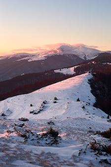 Zonsondergang winterlandschap met houten huizen in besneeuwde bergen
