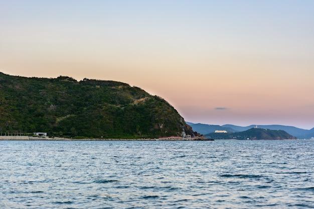 Zonsondergang, zand, heldere turquoise zee, koraalriffen aan de kust van xiaodonghai bay in de zuid-chinese zee. sanya, eiland hainan, china. natuur landschap.