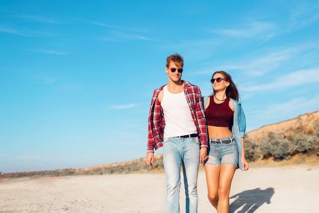 Zonsondergang, zandstrand, een liefdevol hipsterpaar loopt omarmd op het verlaten strand tijdens een dag op het strand op vakantie. stijlvolle zomerkleding dragen. felle kleuren.