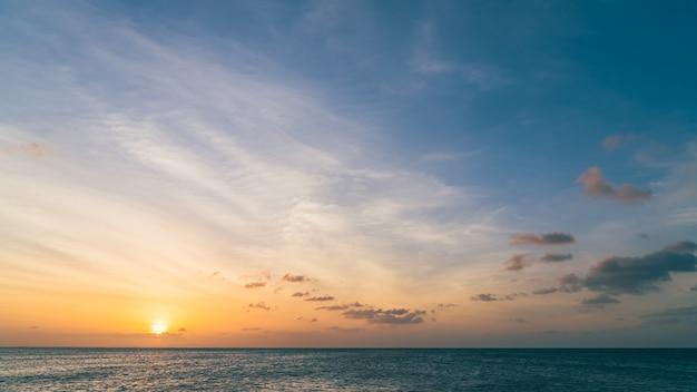 Zonsonderganghemel boven zee in de avond met kleurrijk oranje zonlicht