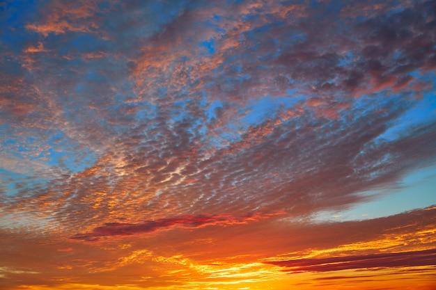 Zonsonderganghemel met oranje wolken over blauw