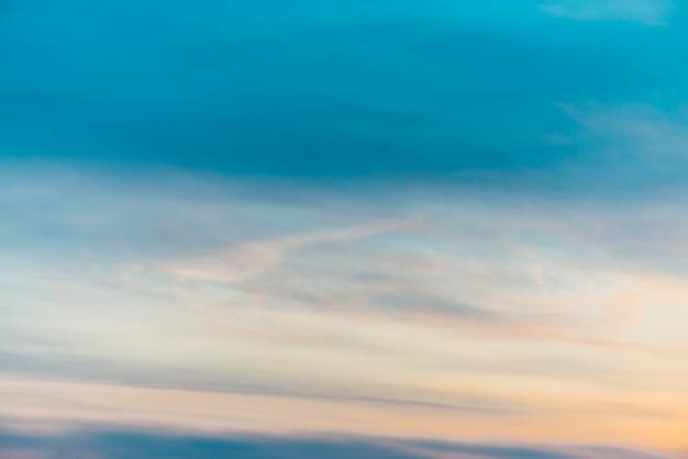 Zonsonderganghemel met oranjegele lichte wolken.