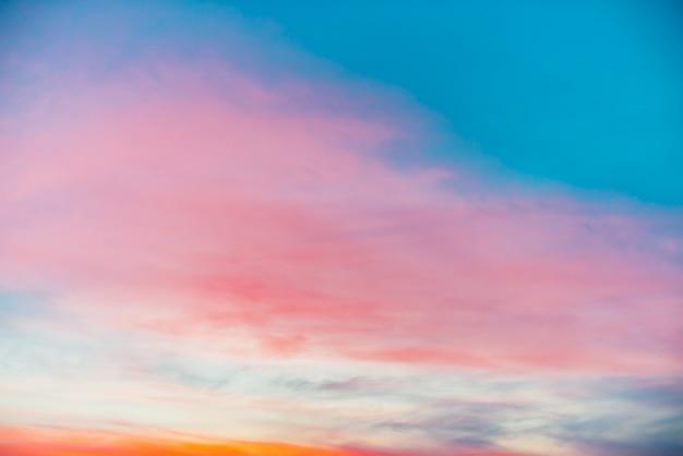 Zonsonderganghemel met roze oranje lichte wolken. kleurrijk vloeiend blauw luchtverloop.