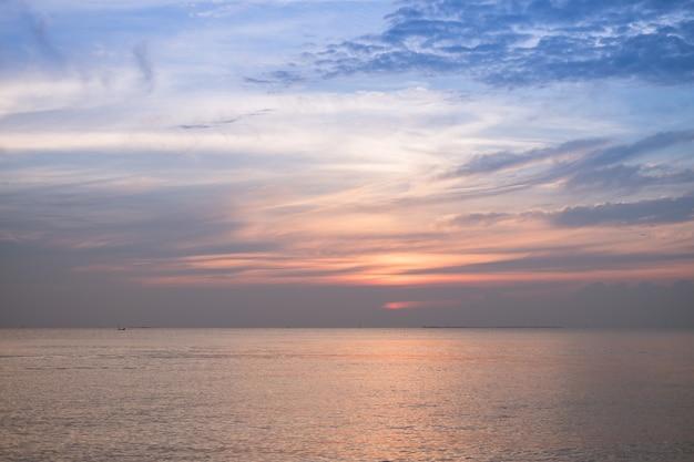Zonsonderganghemel met schemering op de strandachtergrond.