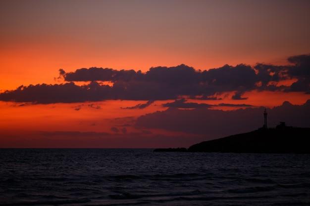 Zonsonderganghemel met wolken boven de zee in de avond na zonsondergang natuurlijke schoonheid in het donker de horiz...