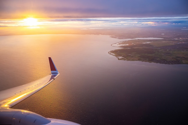 Zonsonderganghemel op vliegtuigvenster over kopenhagen, denemarken in vrijdagavondvlucht