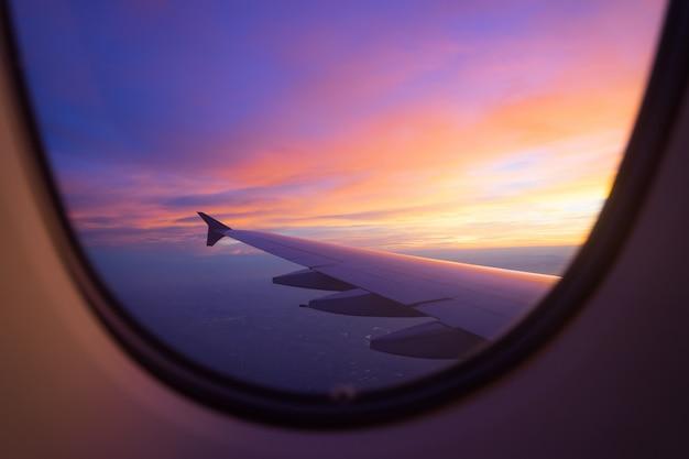 Zonsonderganghemel van het vliegtuigvenster