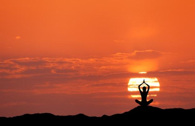 Zonsonderganglandschap met meisje het praktizeren yoga op de heuvel