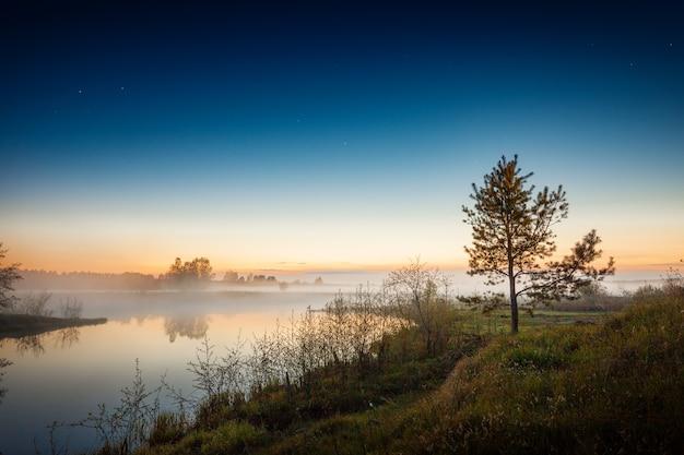 Zonsonderganglandschap met rivieroever