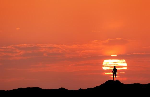 Zonsonderganglandschap met silhouet van een man