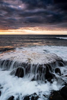 Zonsonderganglandschap op het strand met zee-oceaan en golven op de achtergrond - dramatische lucht met zon en wolken - schemerlicht en horizon