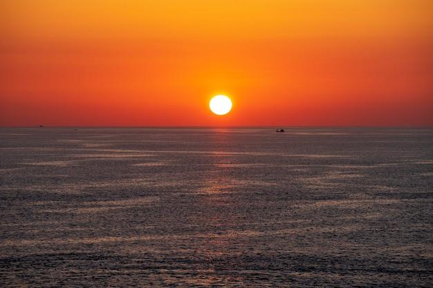 Zonsondergangmening van promthep-kaap, phuket-eiland, zuid-thailand, met mooie orang hemel en kleine vissersboot en jacht.