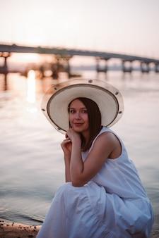 Zonsondergangpicknick bij de brug over de rivier kaukasische ontspannen vrouw in een witte jurk en hoed