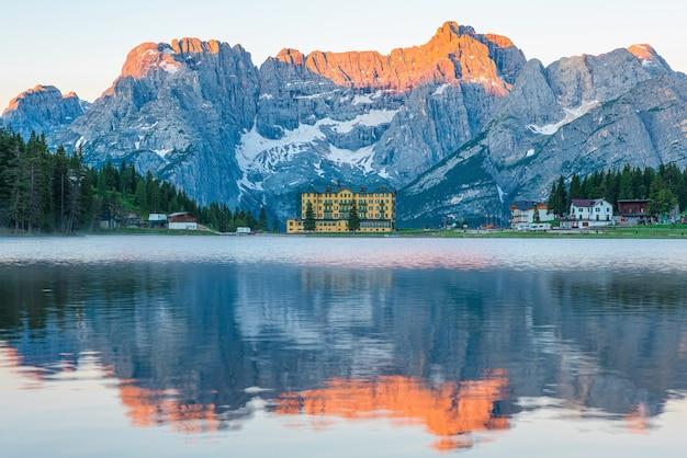 Zonsopgang bij het misurina-meer in de bergen van de dolomieten in italië in de buurt van auronzo di cadore met de sorapiss-berg op de achtergrond. zuid-tirol, dolomieten